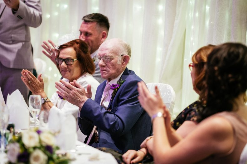 grandfather clapping during a wedding speech