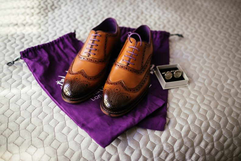 grooms shoes on bed