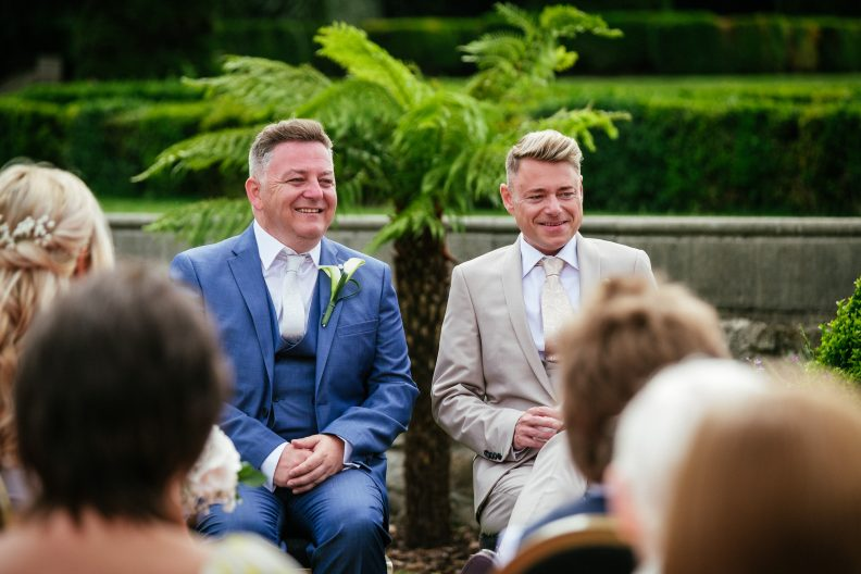 2 grooms sitting during their gay ceremony