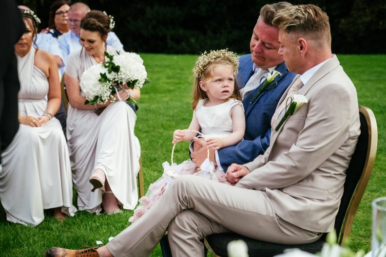 2 grooms interacting with flower girl during their gay ceremony