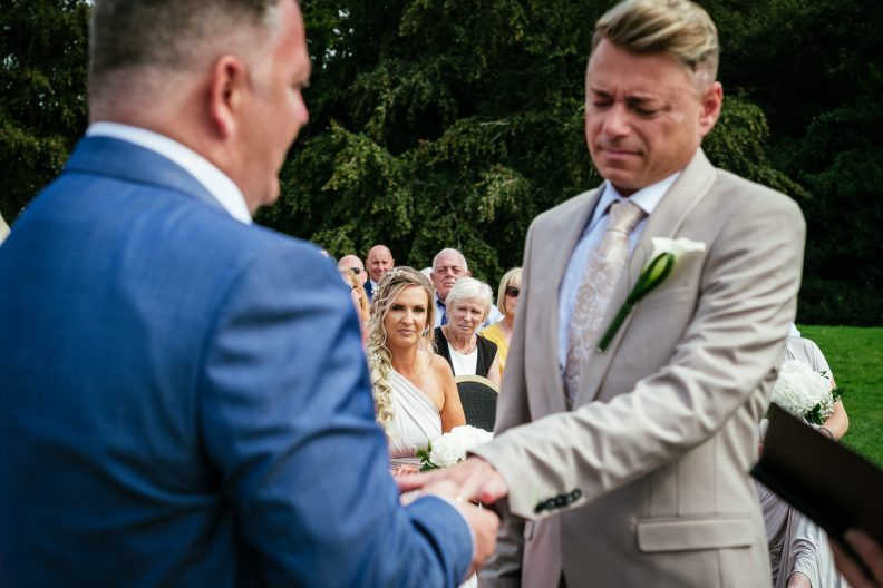 bridesmaid looking intently at 2 grooms