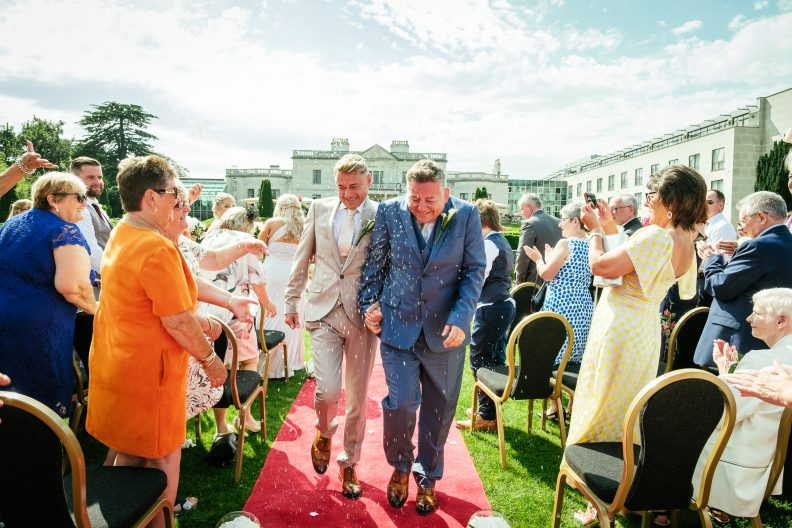 2 grooms walking down aisle being showered with rice during their Outdoor Gay Wedding at Radisson Blu St Helens