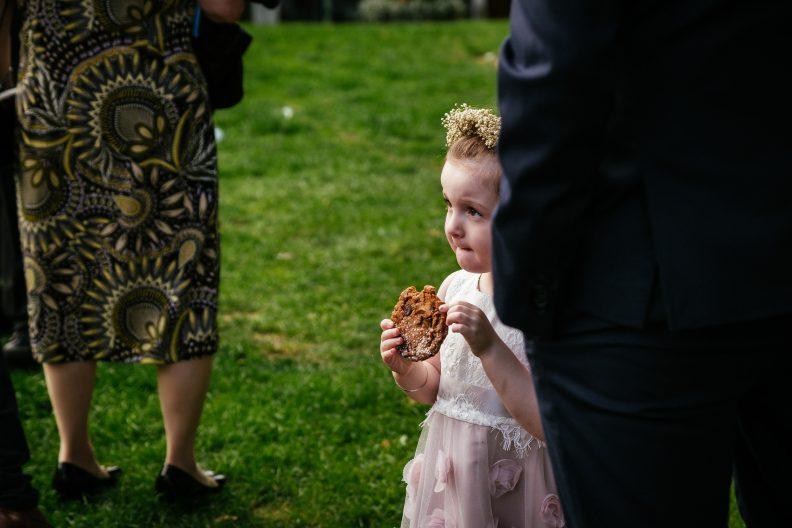 kid at wedding eating a cookie