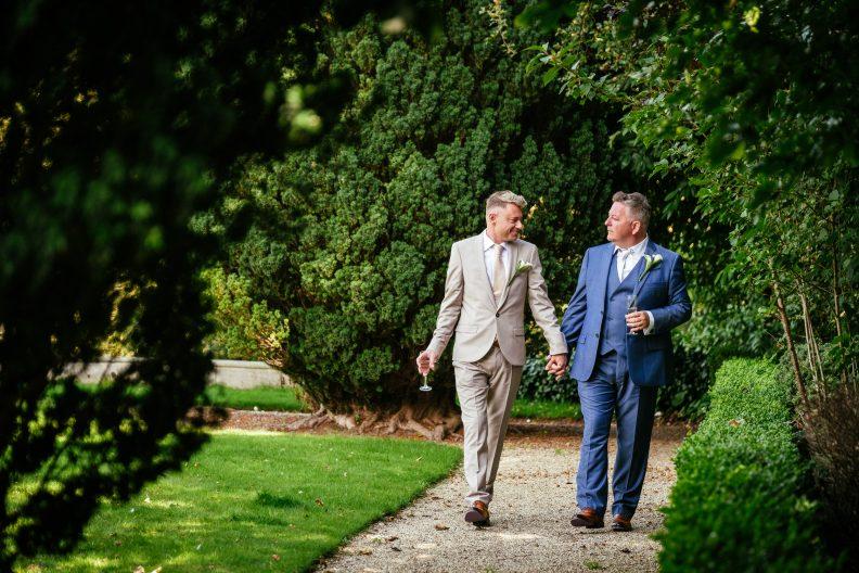 2 grooms strolling in garden