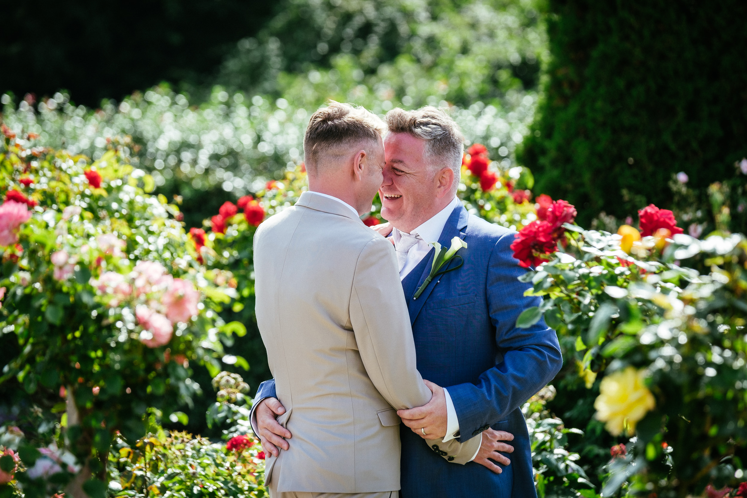 2 grooms laughing during their gay wedding