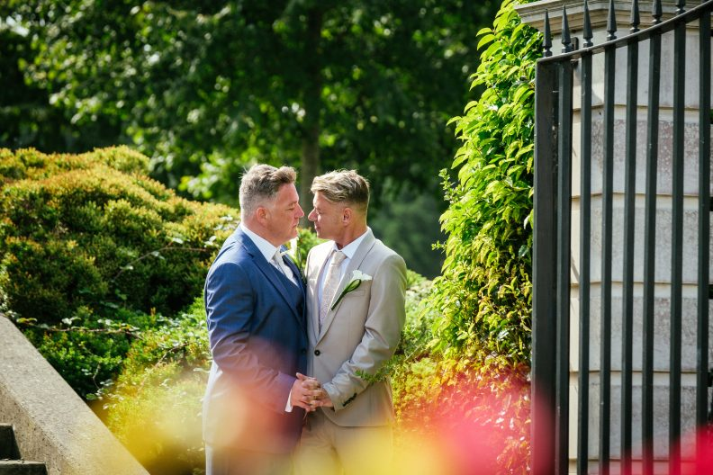 2 grooms looking at eachother during their gay wedding