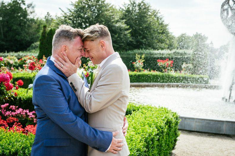 2 grooms cuddling during their gay wedding