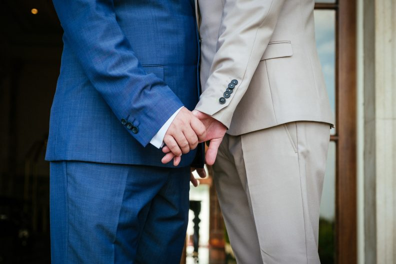 2 grooms holding hands during their gay wedding