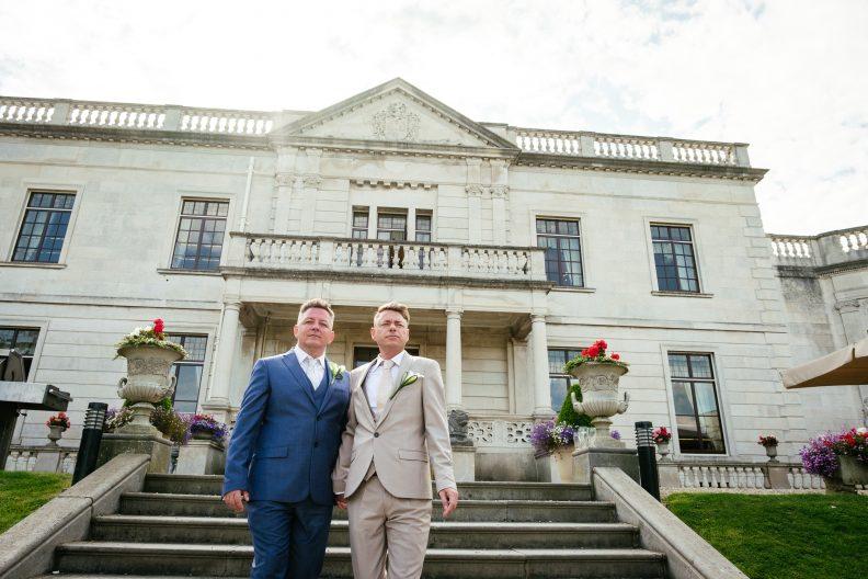 2 grooms walking down steps during their gay wedding