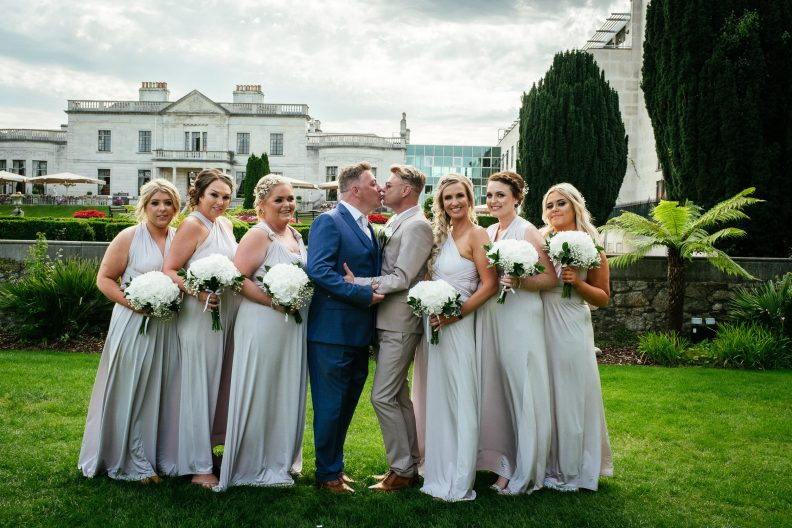 2 grooms kissing with their bridesmaids at their gay wedding