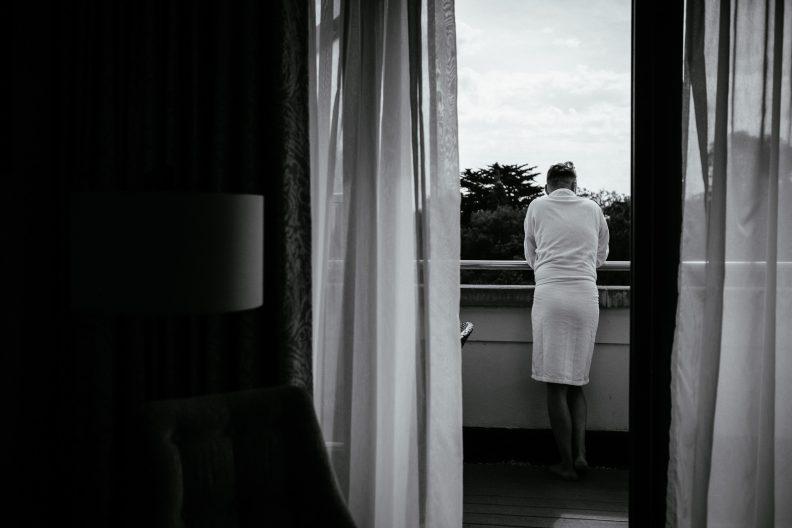 groom in nightrobe on balcony of hotel