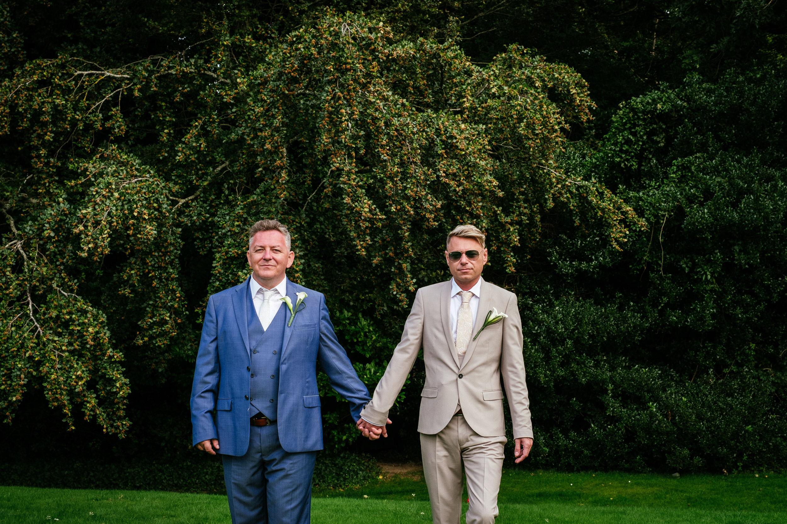 2 gay grooms looking at camera holding hands