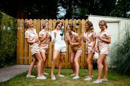 groupe of bridesmaids in pyjamas laughing and drinking champagne