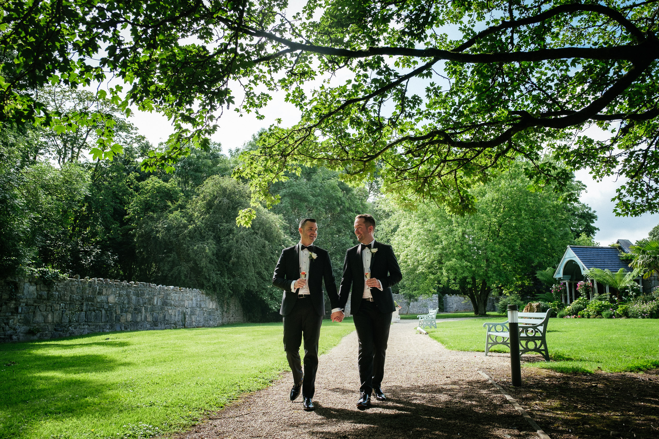 gay grooms walking hand in hand at Johnstown House estate