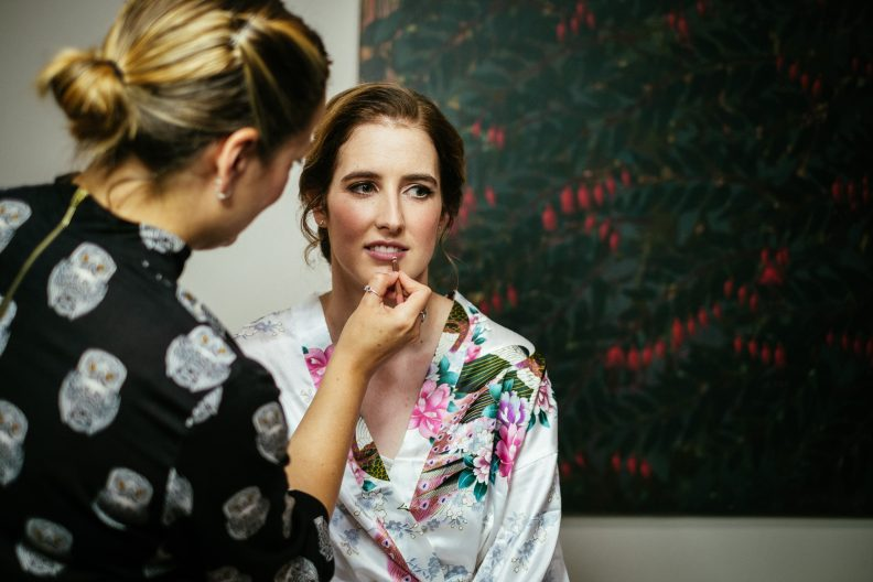 bride getting lip gloss put on