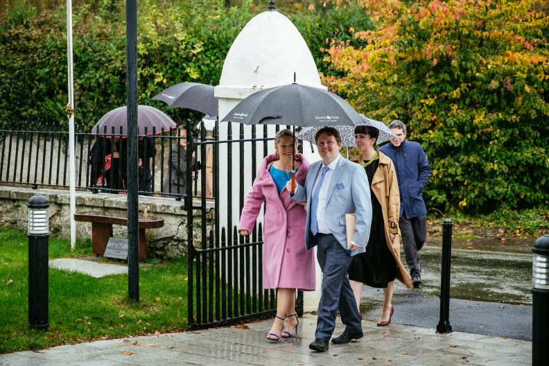 guests arriving at church holding umbrellas