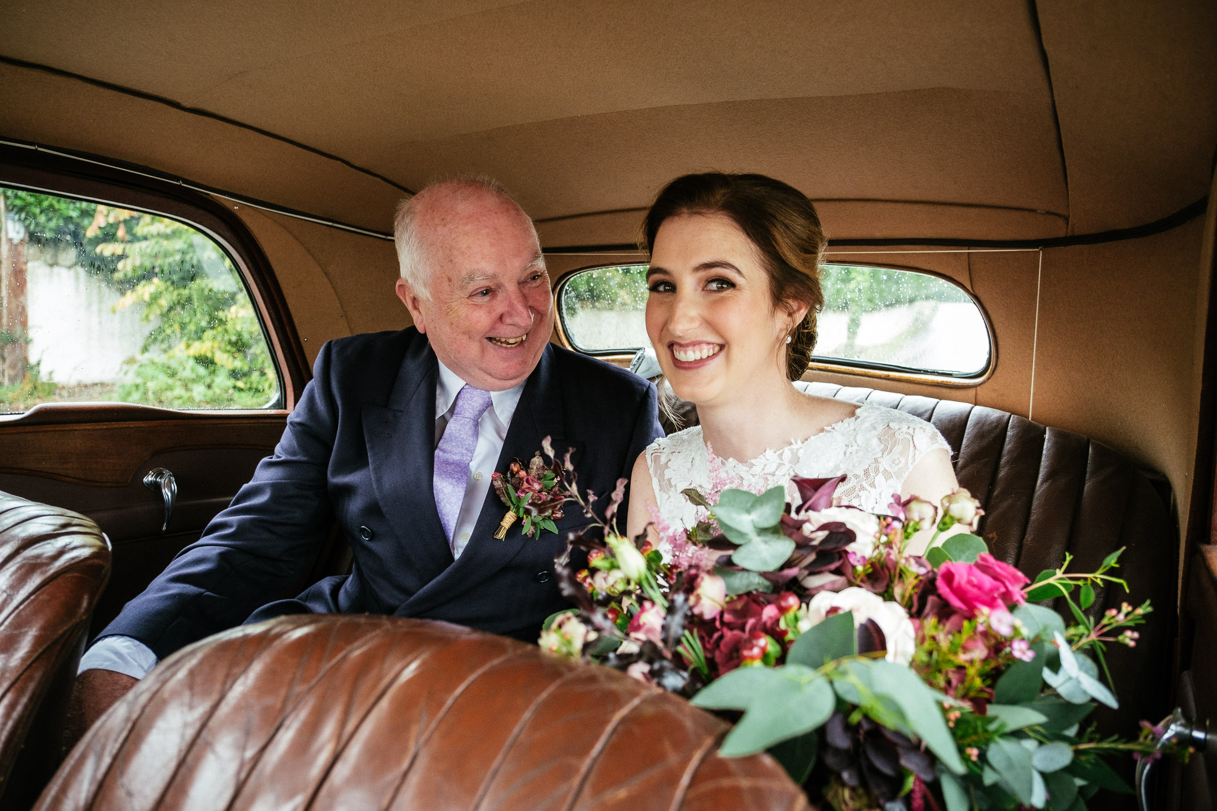 bride with her dad in wedding car