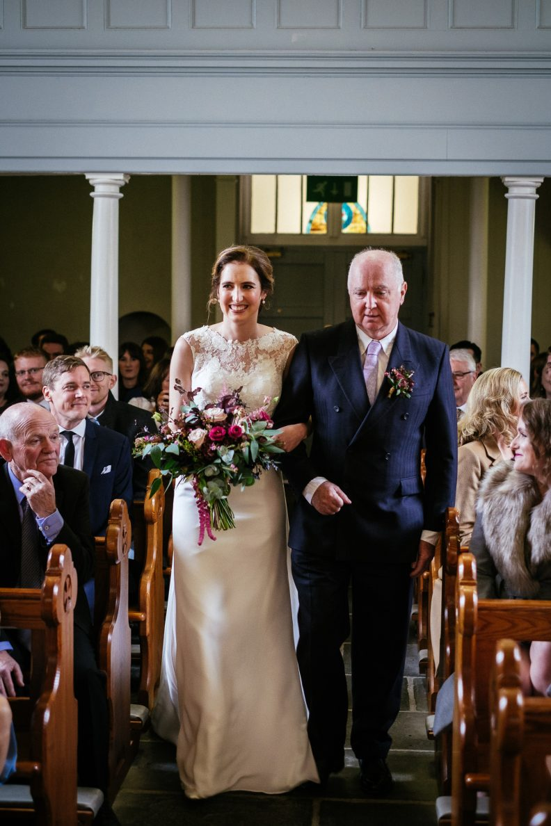 bride walking with her dad down the church aisle