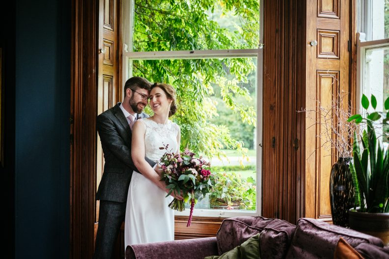 bride and groom by a window at tinakilly house