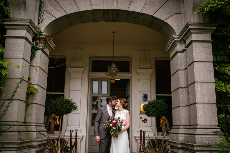 bride and groom kissing in the doorway of tinakilly house