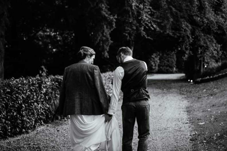 bride wearing grooms jacket and groom walking in gardens of tinakilly house