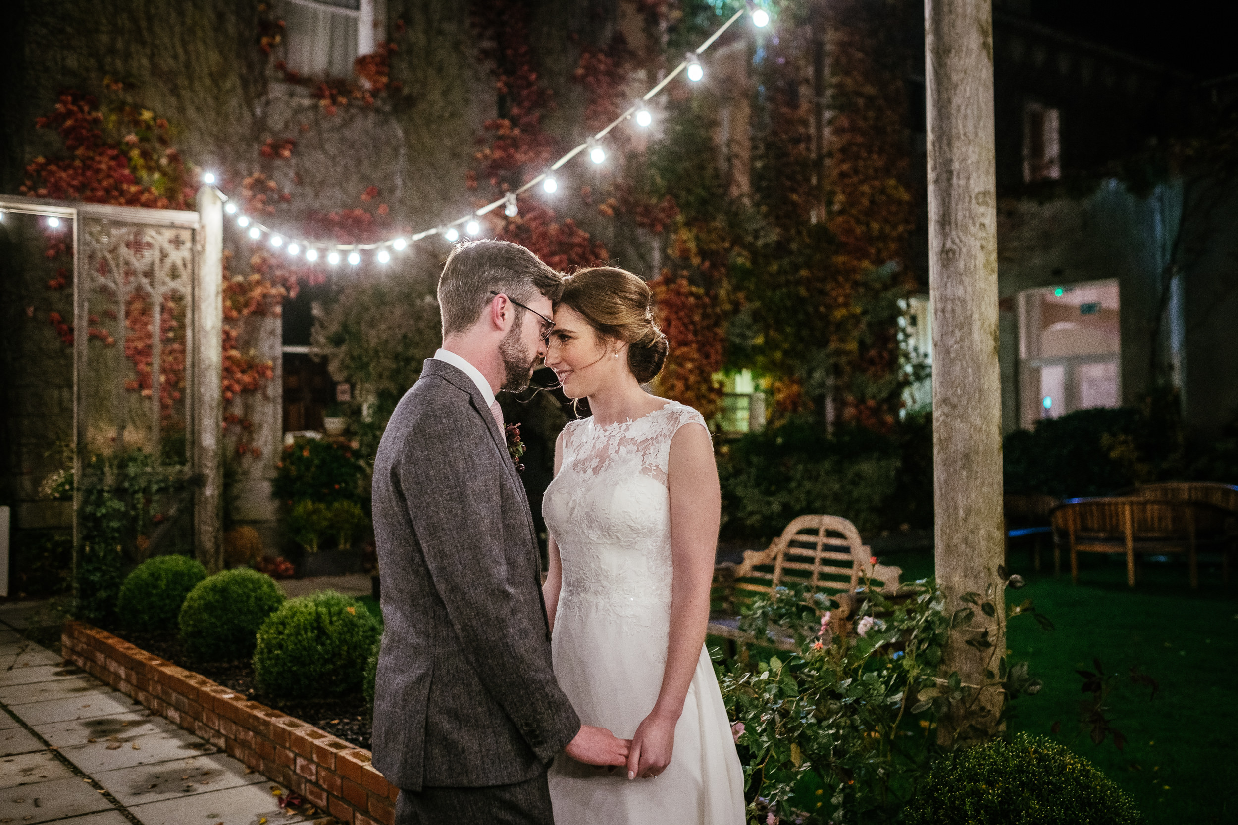 bride and groom hugging under the outdoor fairy lights during their Autumn Wedding at Tinakilly House