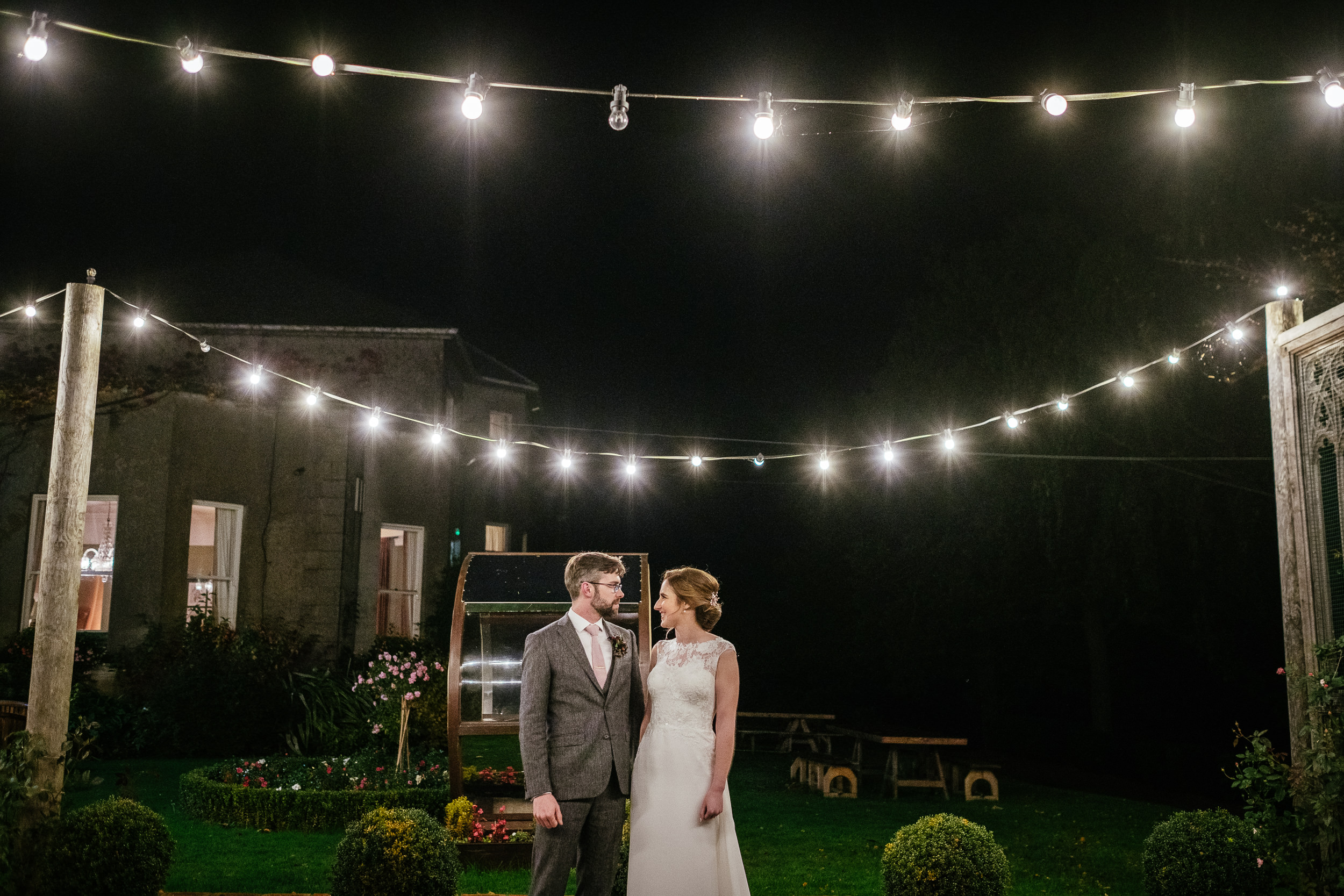 bride and groom standing under the outdoor fairy lights during their Autumn Wedding at Tinakilly House