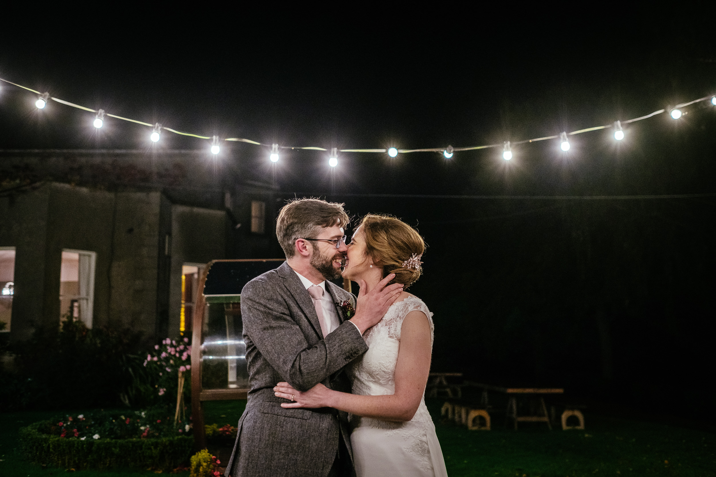 bride and groom kissing at night under the outdoor fairy lights during their Autumn Wedding at Tinakilly House