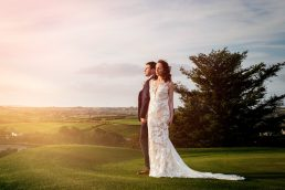 Bride and groom standing looking into the setting sun at their Clonakilty Cork Wedding