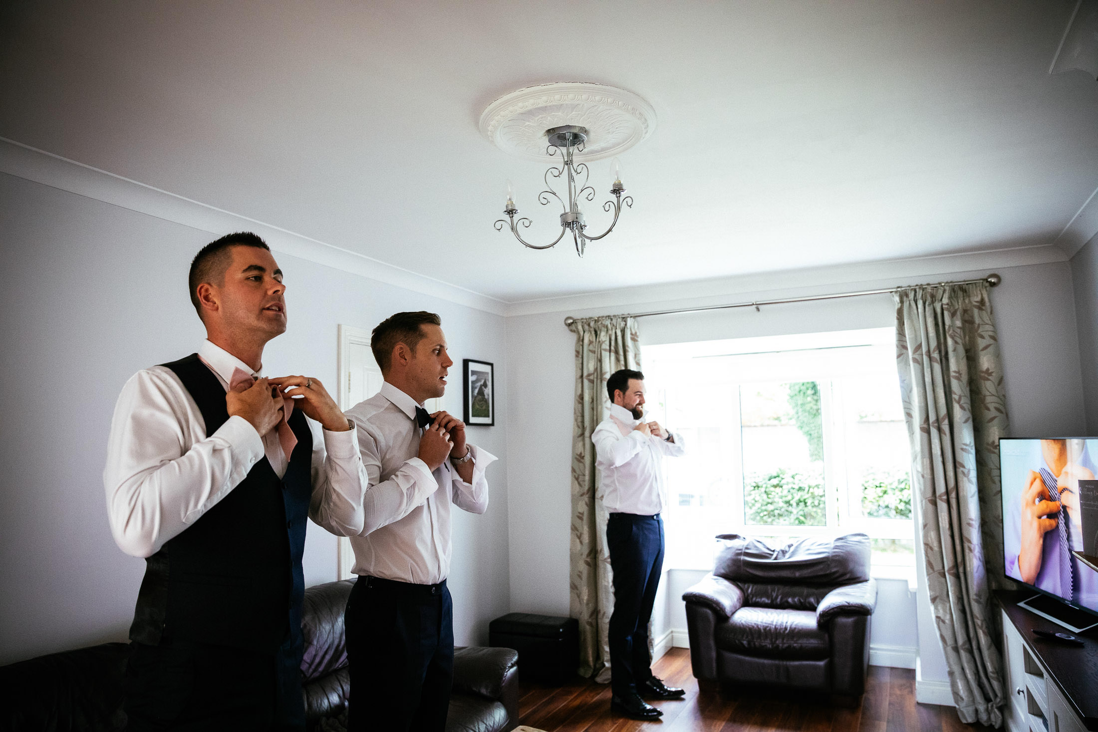 groomsmen tying their bow ties