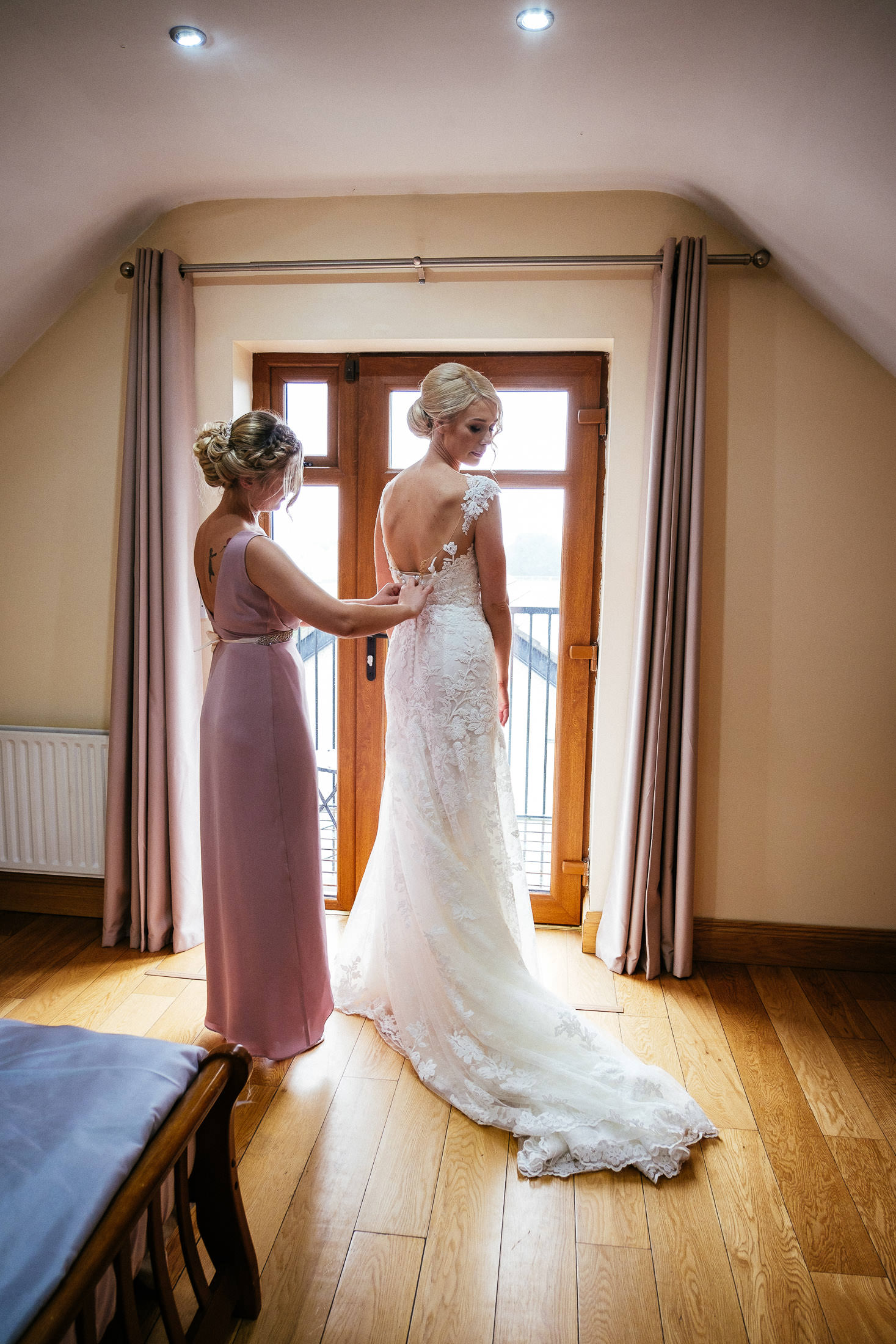 bride being fitted into dress