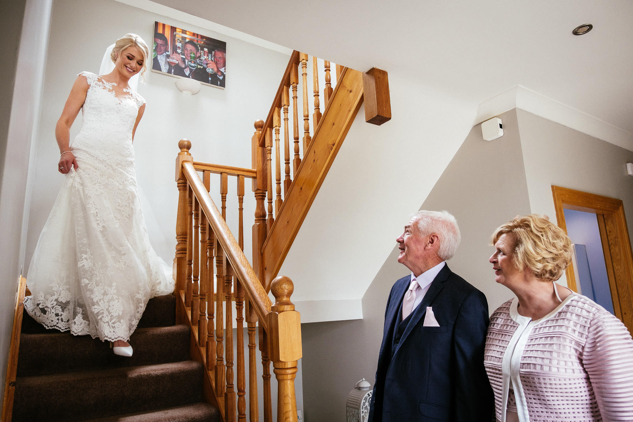 bride walking down stairs to her parents