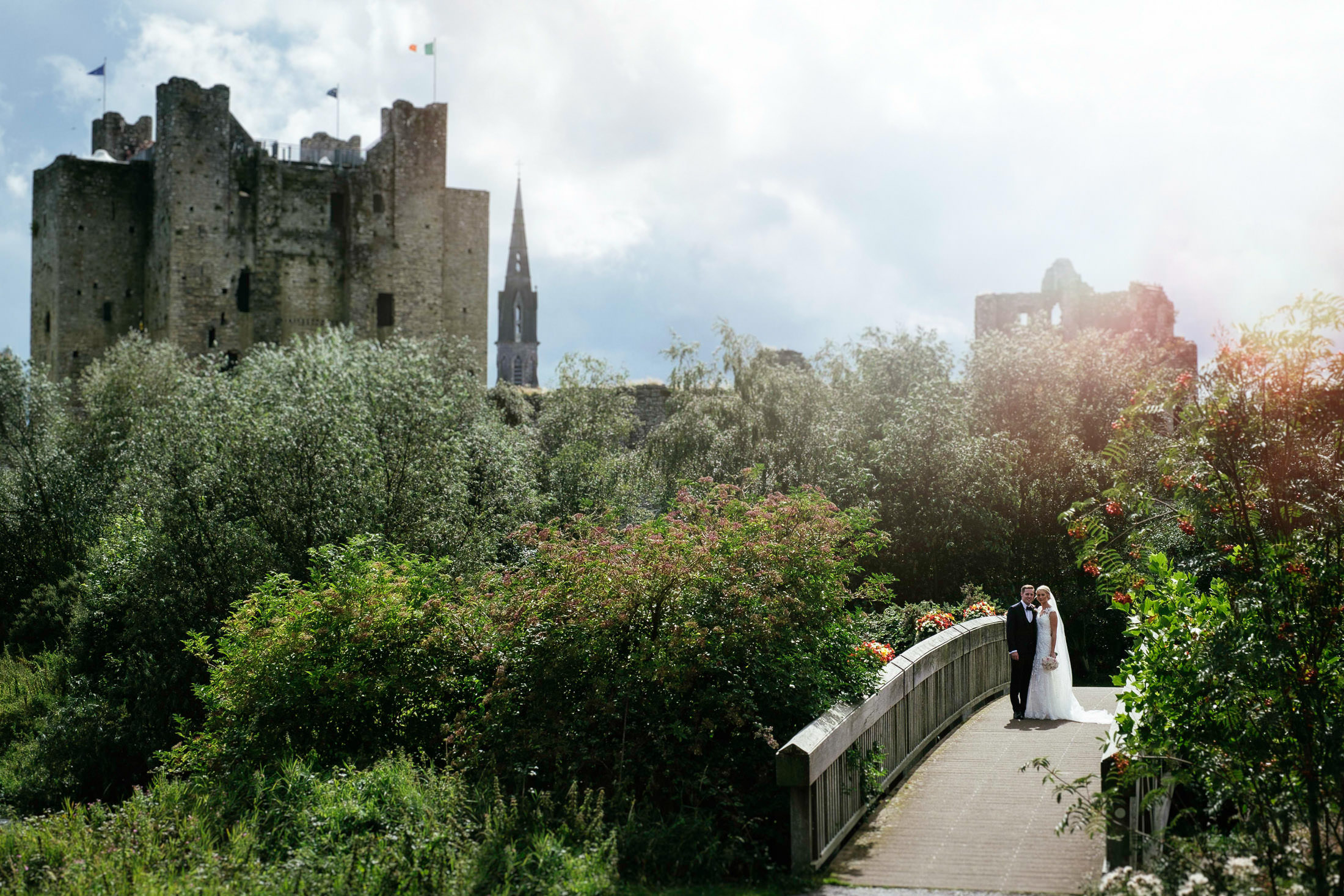 Bride and groom standing on a bridge on their wedding day with Trim castle in the background