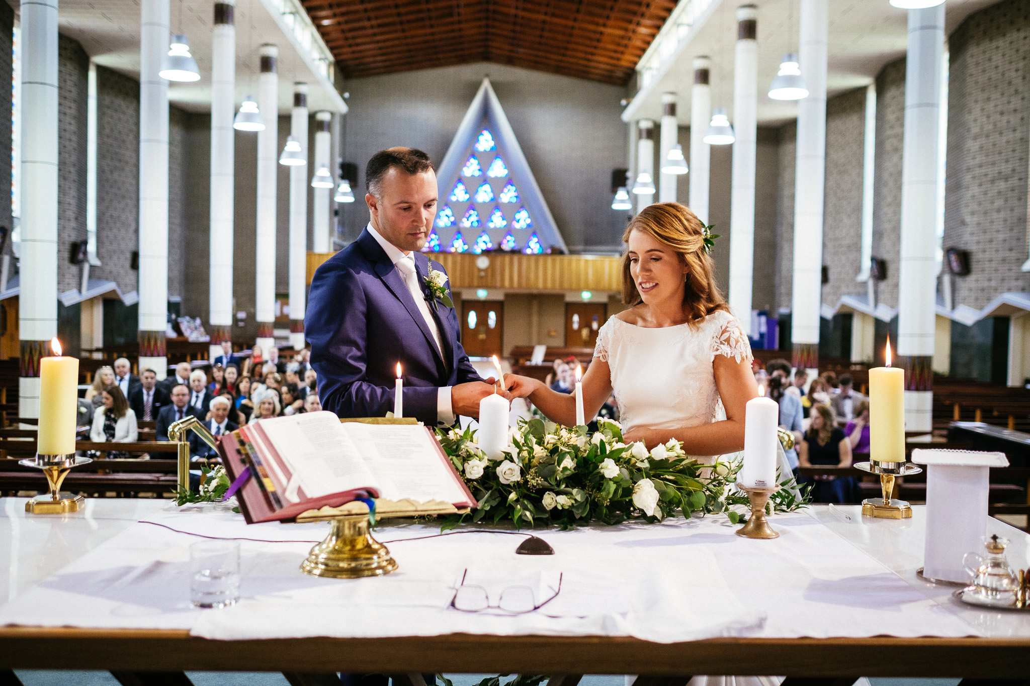 bride and groom lighting candles during their wedding at Our Lady Mother of Divine Grace Church in Raheny