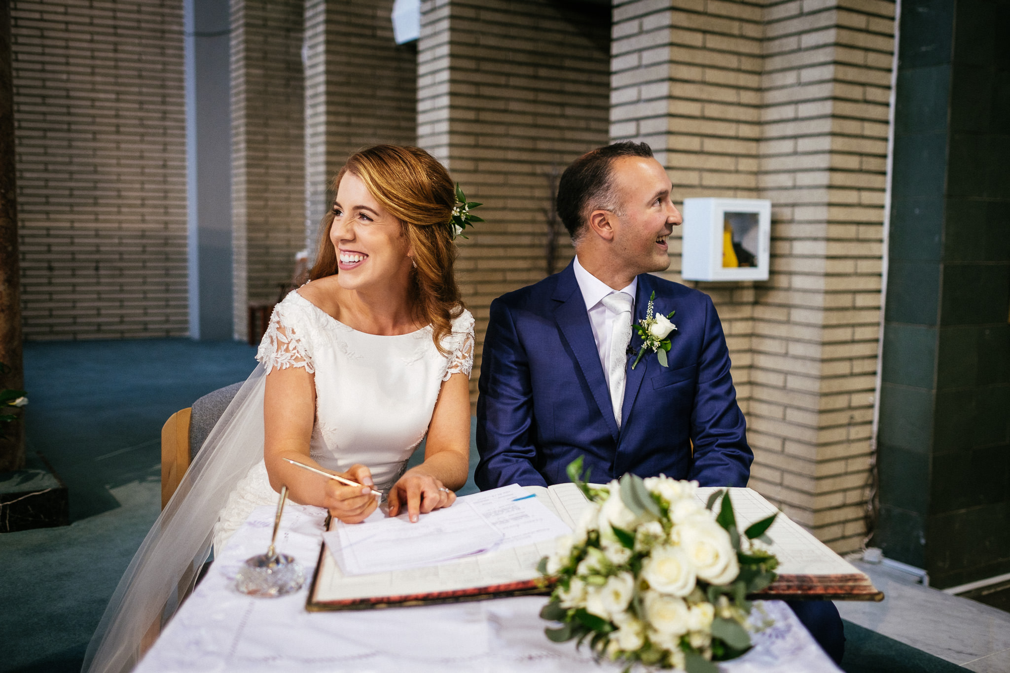 bride signing registar and laughing at Our Lady Mother of Divine Grace Church in Raheny