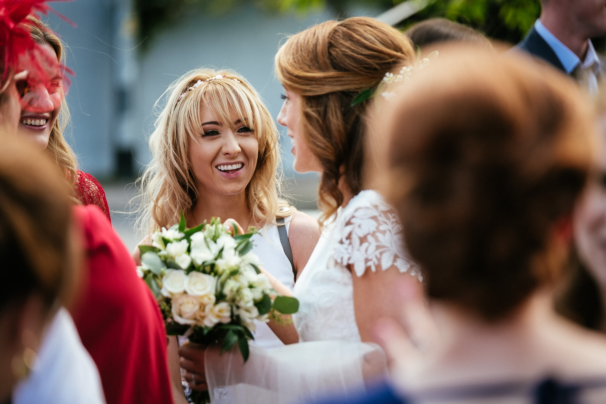female wedding guest laughing at Our Lady Mother of Divine Grace Church in Raheny