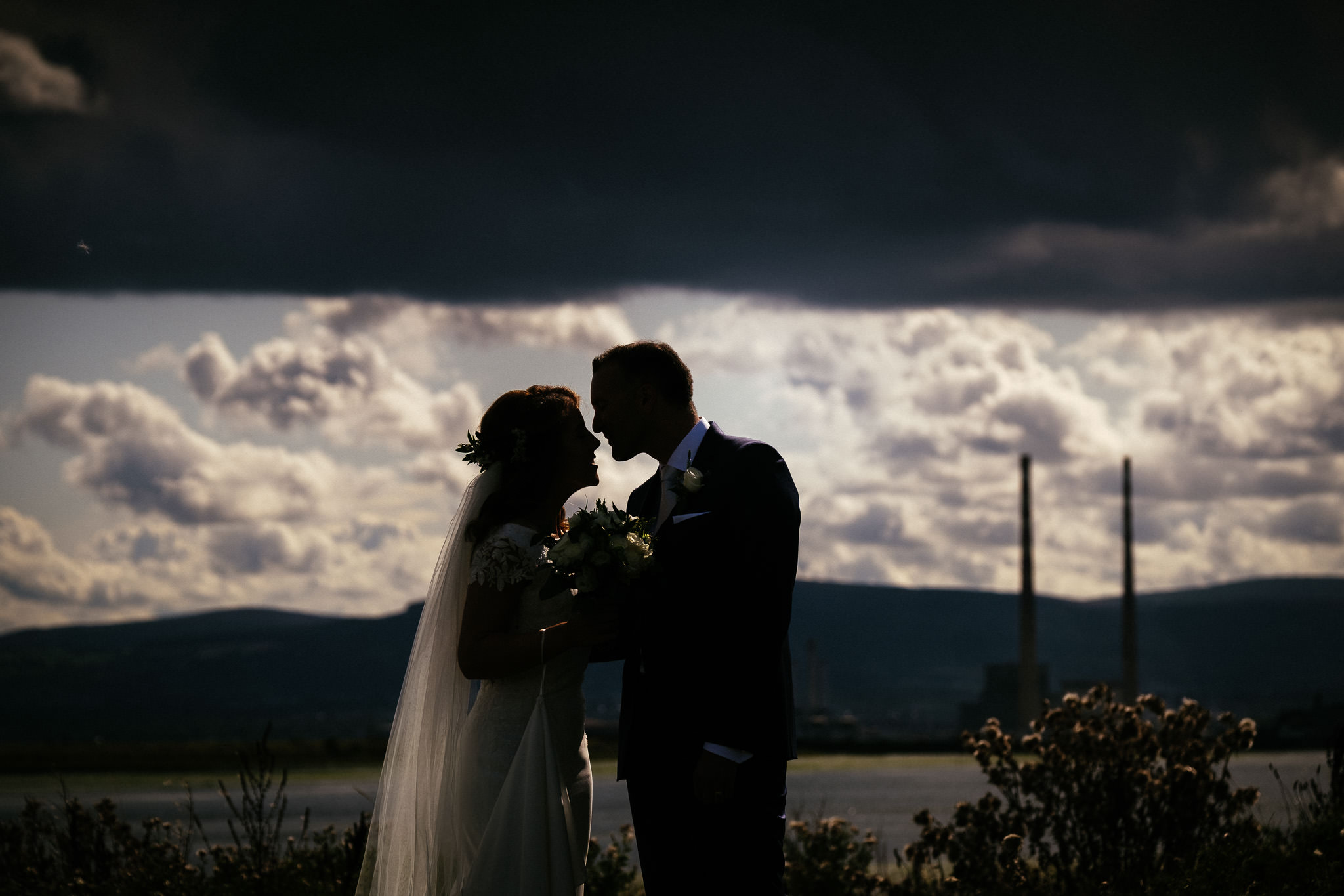 bride and groom with ringsend and Dublin skyline in background