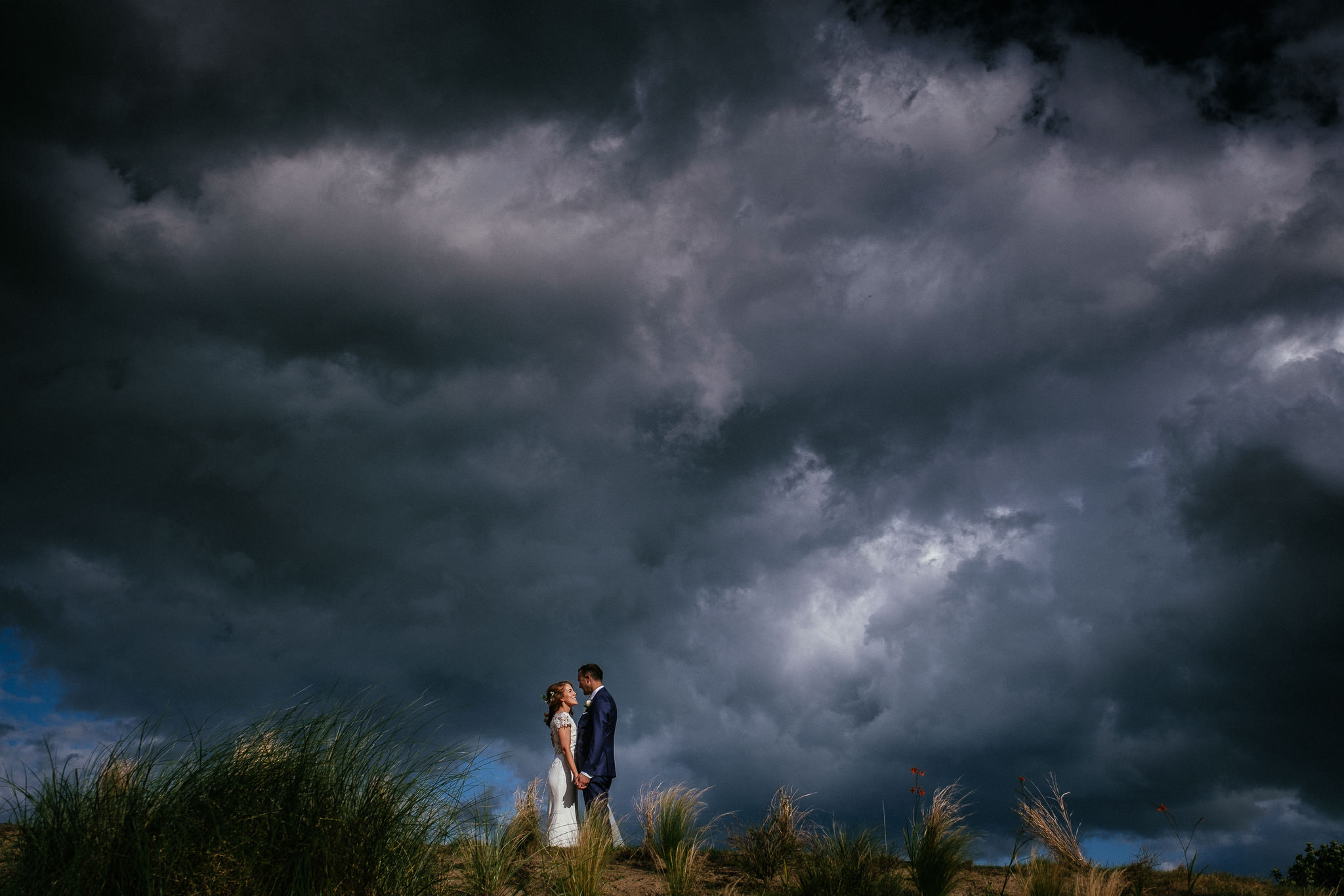 bride and groom holding hands against dramatic storm clouds at their portmarnock hotel wedding