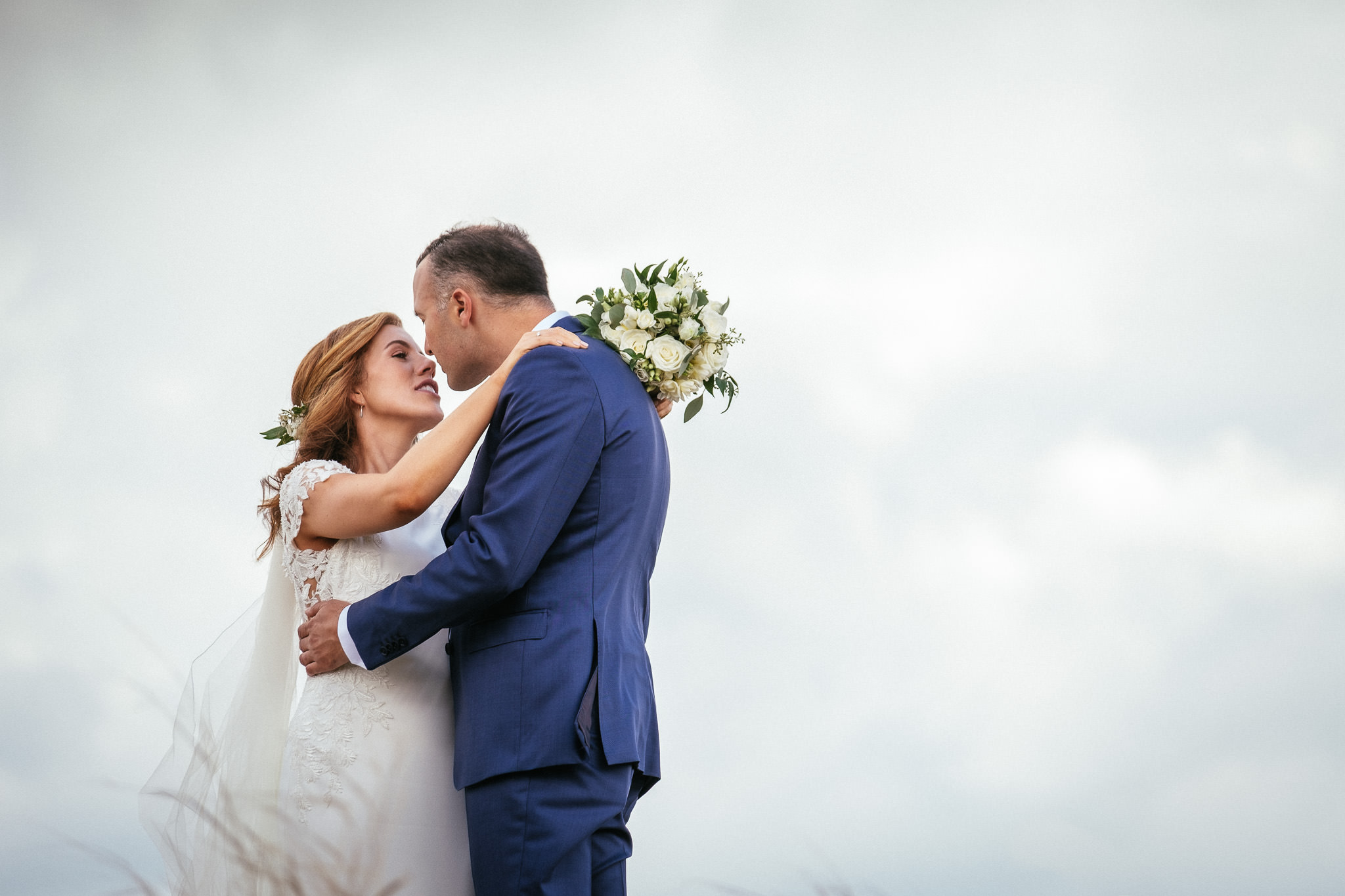 groom standing beside bride on a sand dune at their portmarnock hotel wedding