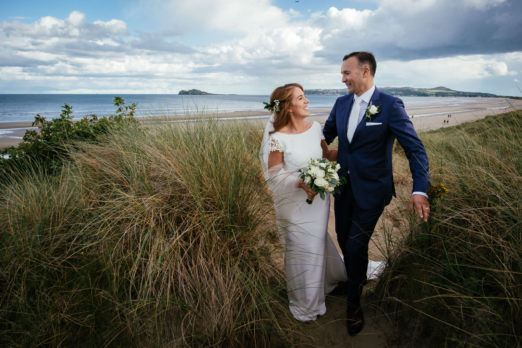 bride and groom walking through sdane dunes at groom standing beside bride on a sand dune at their portmarnock hotel wedding