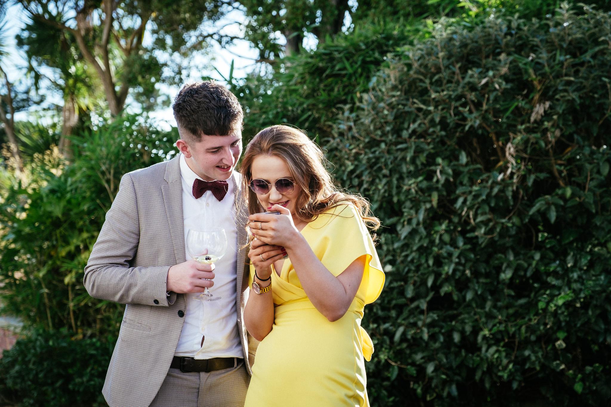 wedding guests looking at their phones