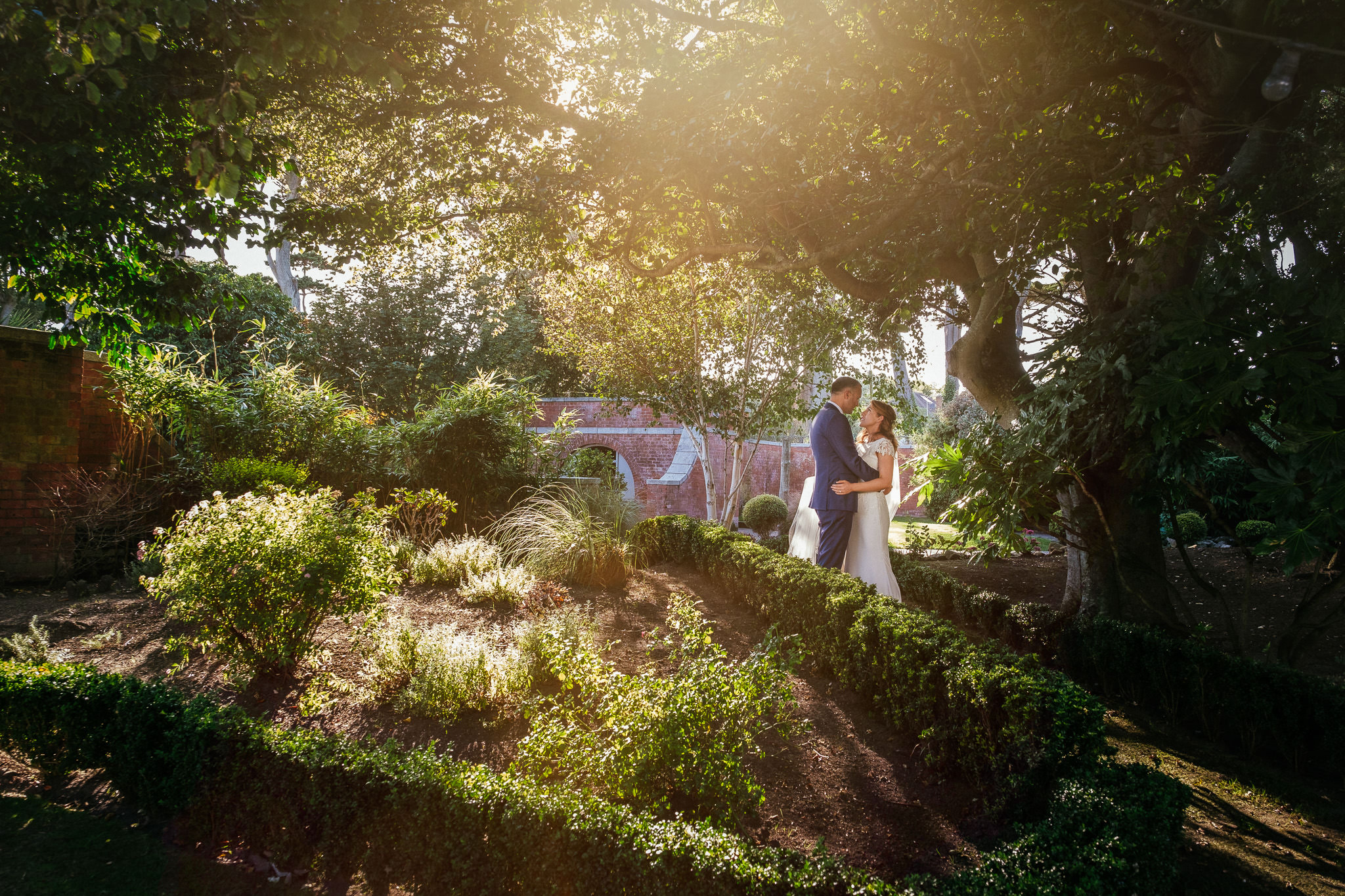 bride and groom with sun filtering through trees portmarnock hotel wedding