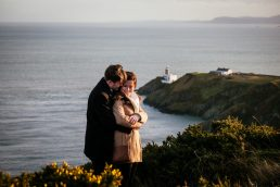 engaged couple hugging on the cliff path at Howth Summit in Dublin with teh Bailey lighthouse in the background