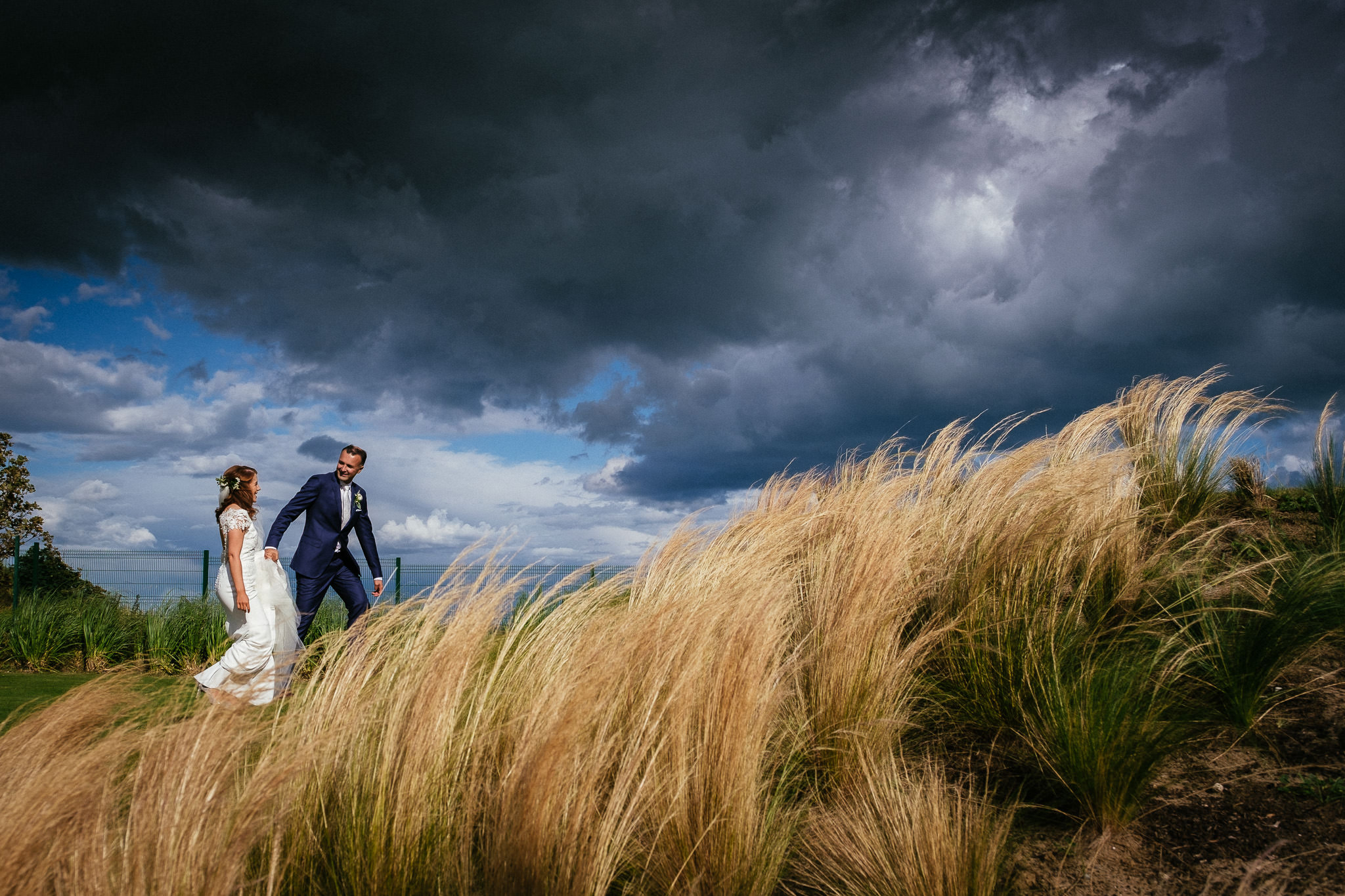 groom leading bride through sand dunes with a dramatic stormy sky in the background