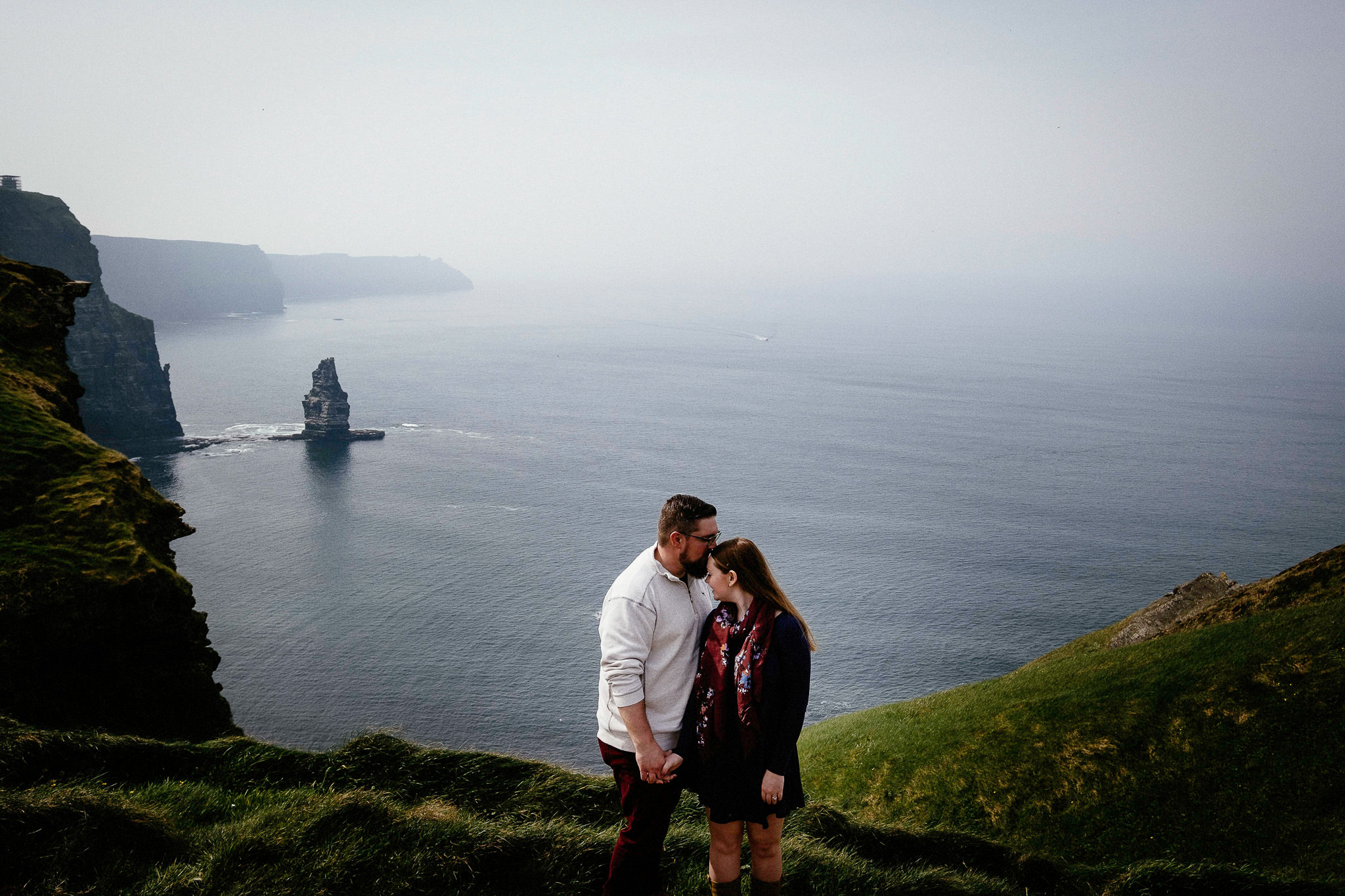 engaged couple kissiing at the Cliffs of Moher