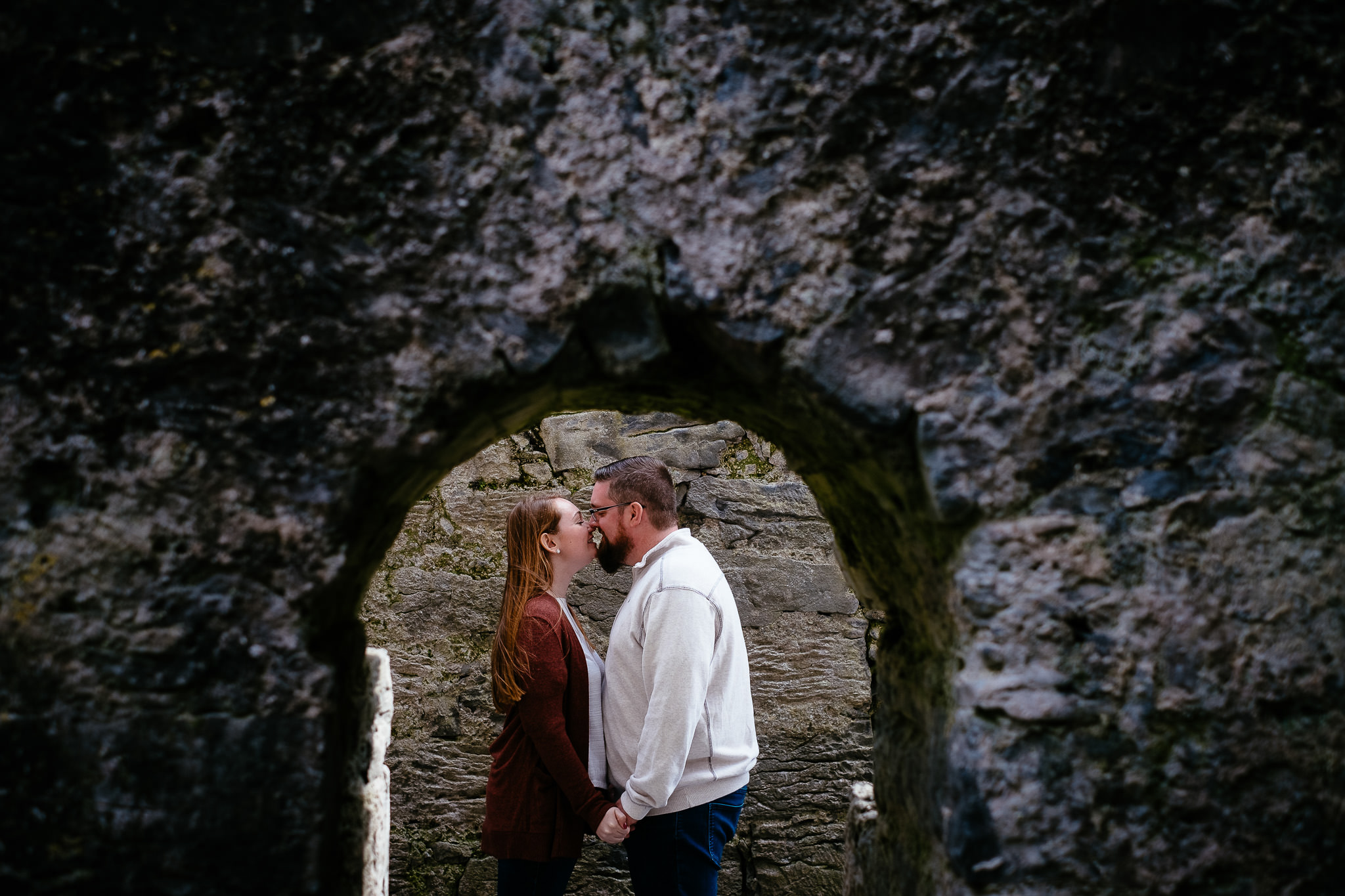 engaged couple kissing at corcomroe abbey