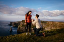 guy one one knee proposing to girlfriend during their engagement shoots at the Cliffs of Moher