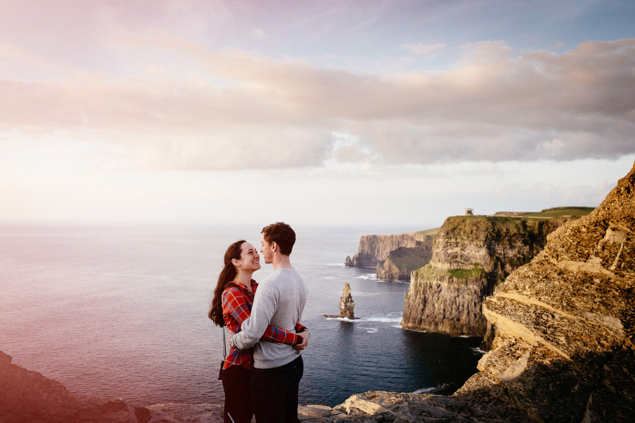 couple embracing as the sun sets at the Cliffs of Moher Ireland