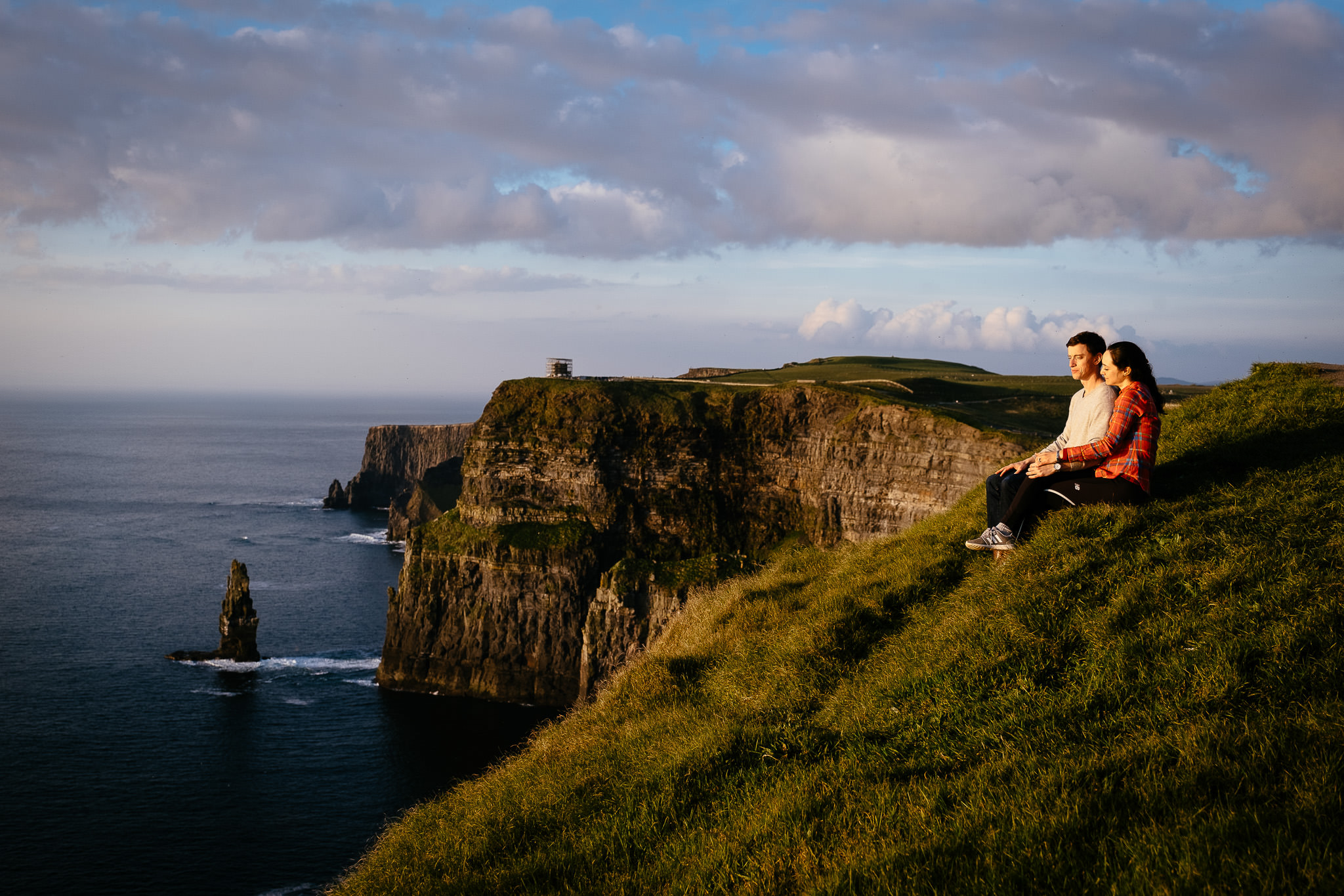engaged couple sitting at the cliff edge at the Cliffs of Moher Ireland