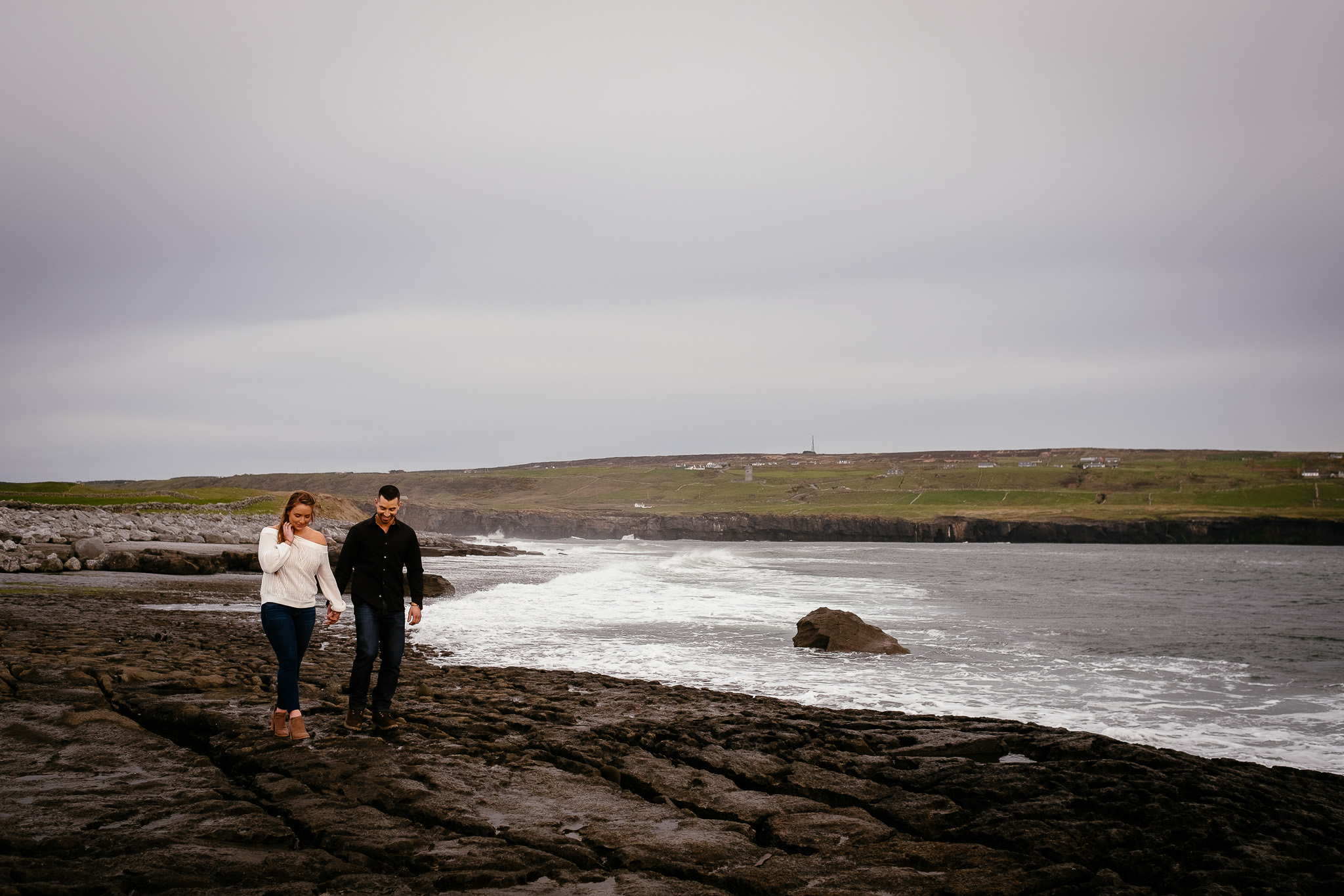 engaged couple walking along shoreline at Doolin beside the Cliffs of Moher Ireland